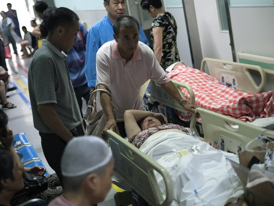 A man pushes his relative through a hallway crowded with patients waiting to receive medical treatment at a Beijing hospital in July 2013. Journalist Wu Si says gray income is just a fact of daily life in China — everyone ranging from teachers and doctors to officials accepts off-the-books payments.
