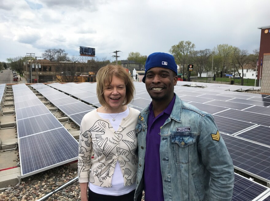 Sen. Tina Smith, D-Minn., and Keith Dent stand in front of the community solar garden on the roof of Shiloh Temple in Minneapolis. Dent helped install the array.