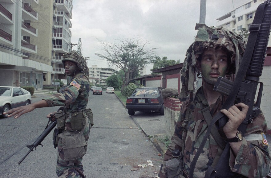 U.S. soldiers direct traffic outside the residence of the Peruvian ambassador to Panama, right rear, in Panama City on Jan. 9, 1990. In December 1989, U.S. President George H.W. Bush sent thousands of troops to Panama to arrest the country's leader, Manuel Noriega.