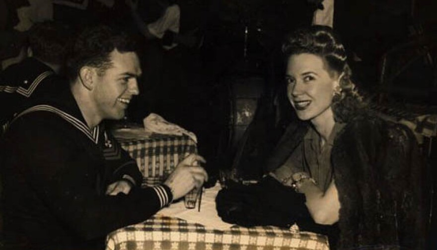 """Creore sits with a sailor at the Stage Door Canteen in New York. """"They were all homesick,"""" she recalls."""