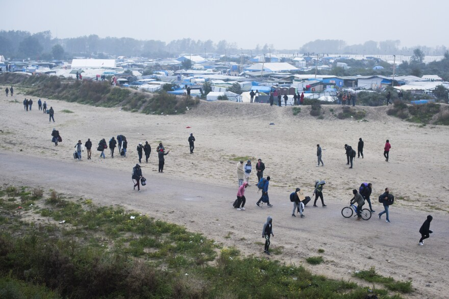 A stream of migrants leaves The Jungle on Monday. Authorities have begun processing and evicting refugees; destruction of the camp is slated to begin Tuesday.