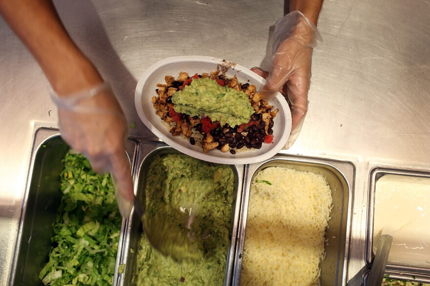 Chipotle restaurant workers fill orders for customers in Miami, Fla., on April 27, 2015, the day that the company announced it will only use non-GMO ingredients in its food.