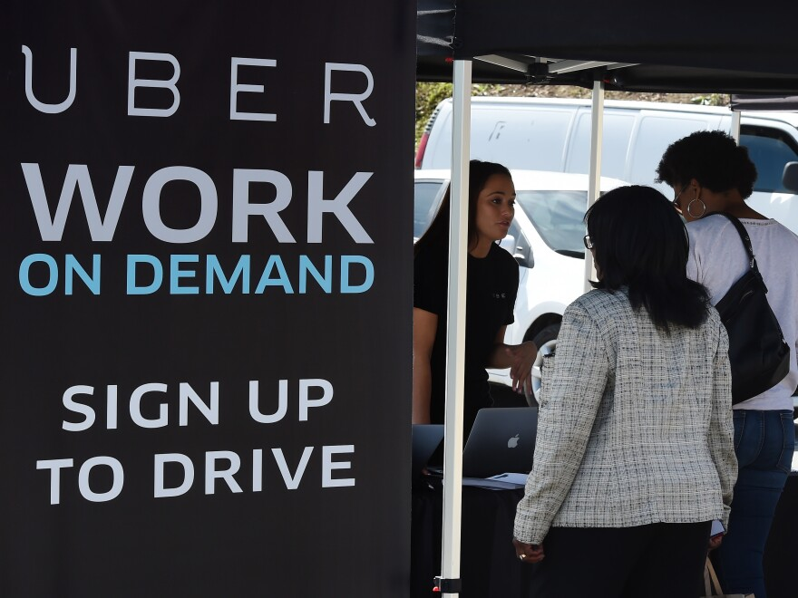 People sign up to become Uber drivers at the first of Uber's 'Work On Demand' recruitment events.