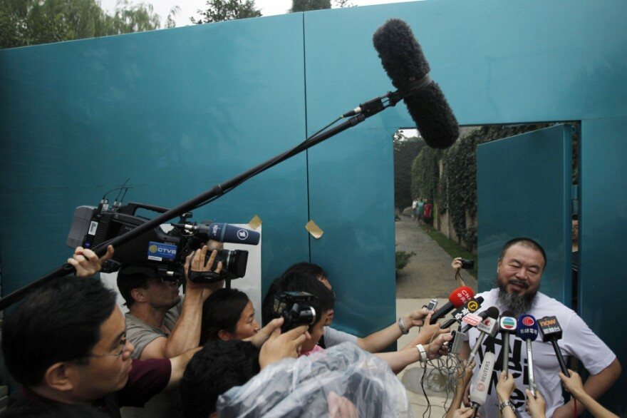 Activist artist Ai Weiwei speaks to journalists gathered outside his home in Beijing, China, Thursday.