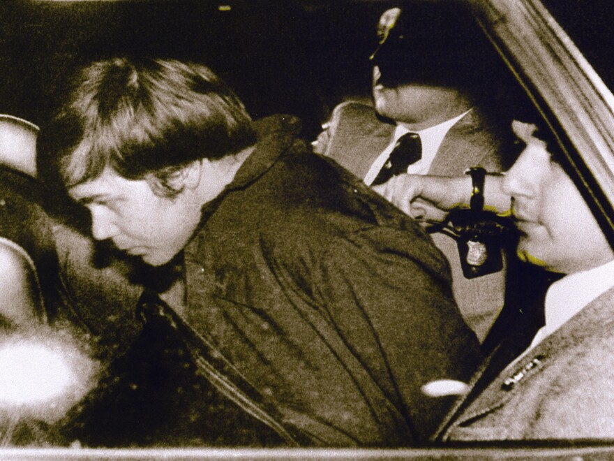 John Hinckley Jr. in 1981, escorted by police in Washington, D.C., following his arrest after shooting and seriously wounding then-President Ronald Reagan. He was found not guilty by reason of insanity.