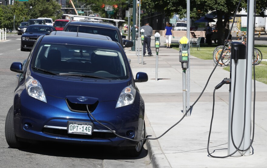 In this Tuesday, June 26, 2018, photograph, a Nissan Leaf charges at a recharge station while parked by the Denver City/County Building in downtown Denver. (AP Photo/David Zalubowski)