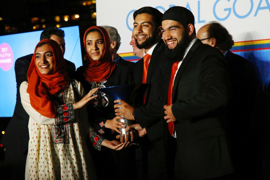 The team that won the Hult Prize poses with their trophy on September 16 at U.N. headquarters. From left: Gia Farooqi, Hanaa Lakhani, Moneeb Mian, and Hasan Usmani. They developed a ride-sharing rickshaw service for refugees in a Pakistan slum.