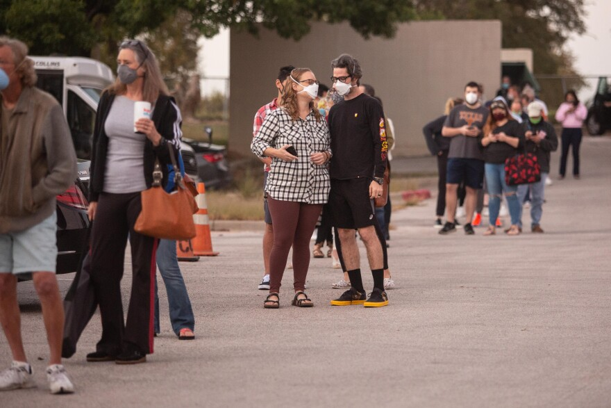 Voters wait in line at the Northwest Recreation Center in Austin to cast ballots Tuesday, the first day of early voting.