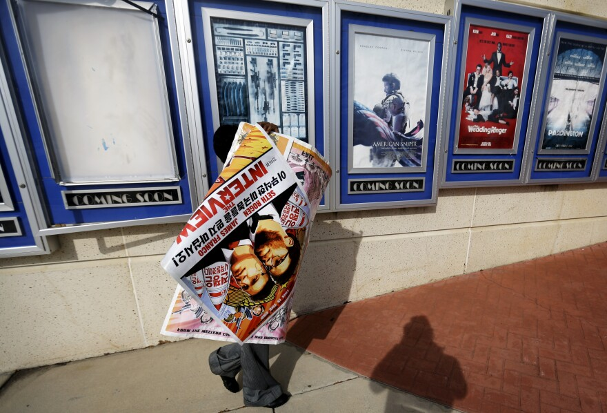 """A worker carries a poster for the movie <em>The Interview</em> away from its display case at a theater in Atlanta. """"It feels like the margin's narrowed about what kind of movies Hollywood will be making,"""" says veteran Hollywood producer Stephanie Striegel."""