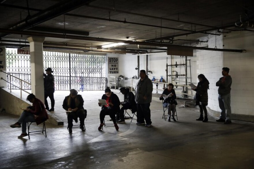 Unionized hospitality workers wait in line in a basement garage to apply for unemployment benefits at the Hospitality Training Academy Friday, March 13, 2020, in Los Angeles. In Oregon, unemployment claims are spiking because of coronavirus-related shutdowns.