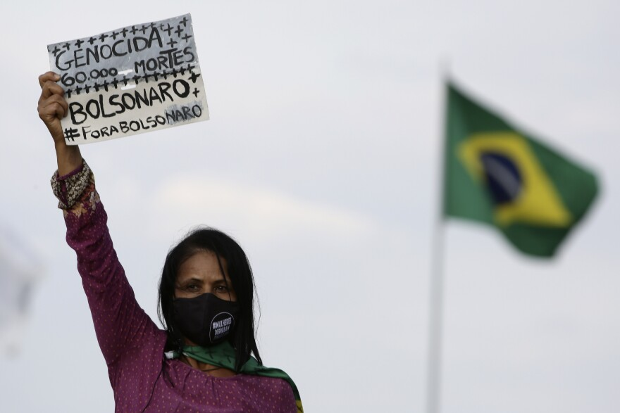"A women's movement activist holds a sign that reads in Portuguese ""Genocide 60 thousand deaths, Bolsonaro out"" during a protest against the government's handling of the pandemic earlier this month."