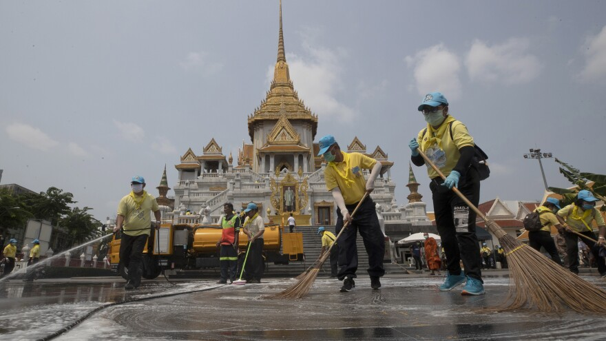 Volunteers clean as a precaution against the new coronavirus at Wat Traimit temple in Bangkok on Wednesday. Thailand's government has enacted stronger measures to combat the spread of COVID-19.