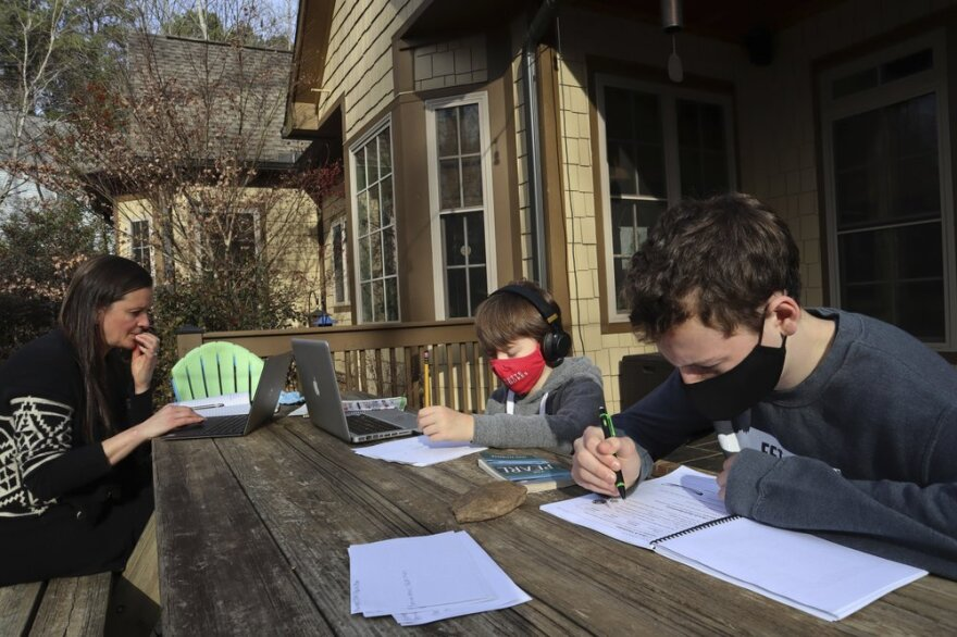Angela Atkins works outside her home in Oxford, Miss., while her two sons, Jess and Billy, work on schoolwork on laptops.