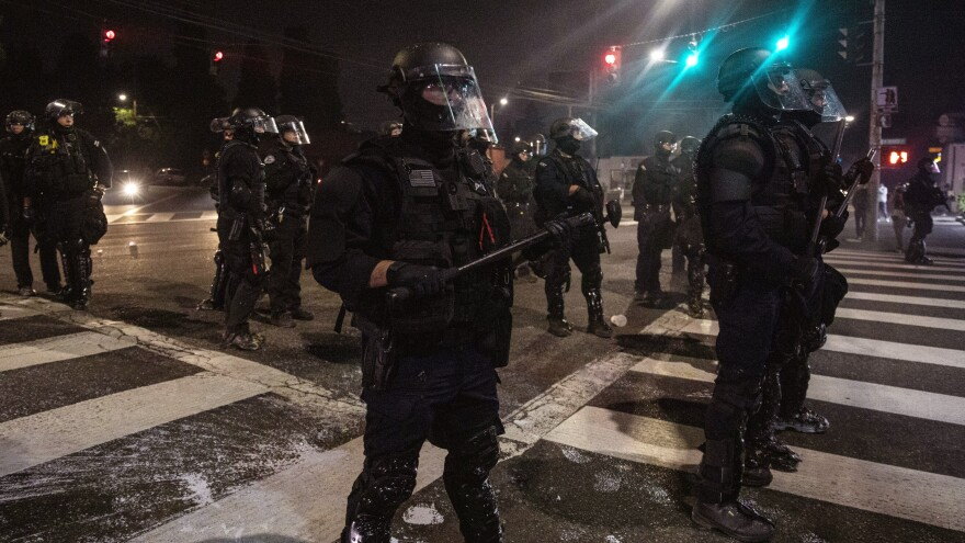 Police stand guard as protesters take to the streets on Sept. 4 in Portland, Ore.