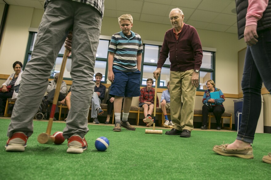 Greg Kintzele, left, and Bill Taylor, right, watch as others play croquet at Graland Country Day School in Denver.