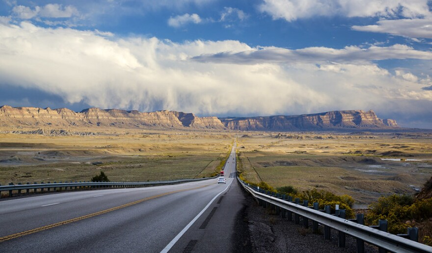 A photo of a road leading to the Book Cliffs up ahead.