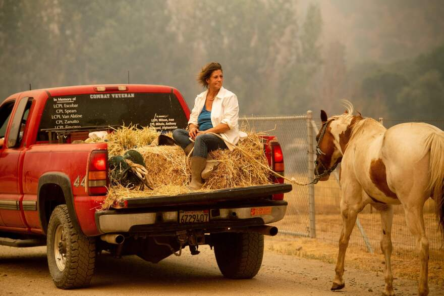 Debbie Prior leads a horse to safety as the Ranch Fire tears down New Long Valley Road near Clearlake Oaks, Calif., on Saturday. The Ranch Fire is part of the Mendocino Complex.