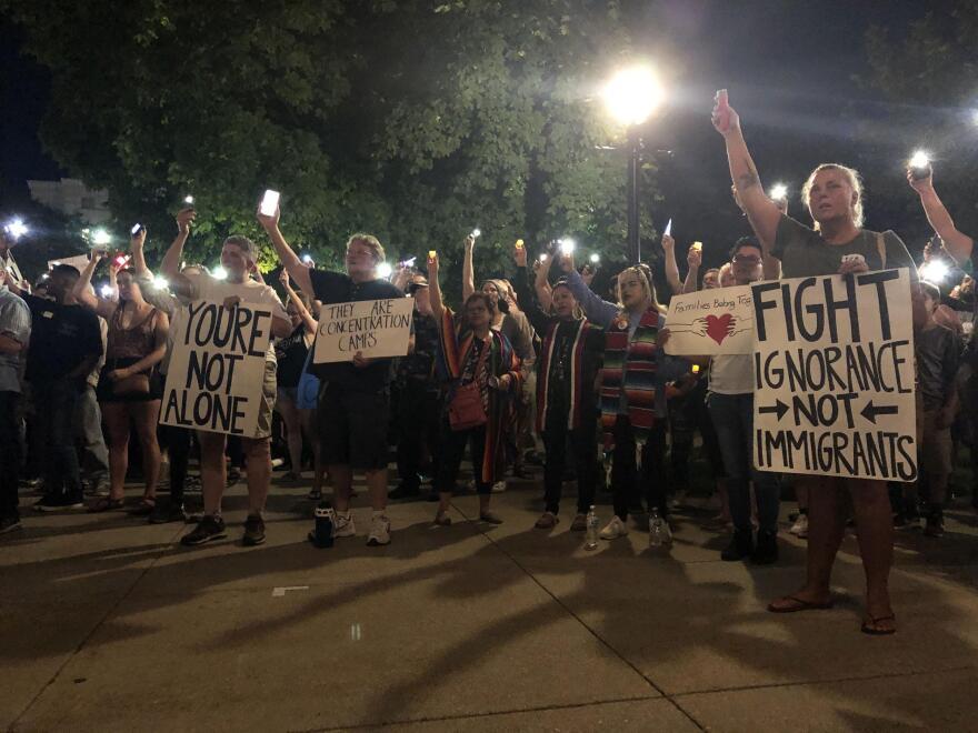 Salt Lake City vigil attendees hold up signs, lights