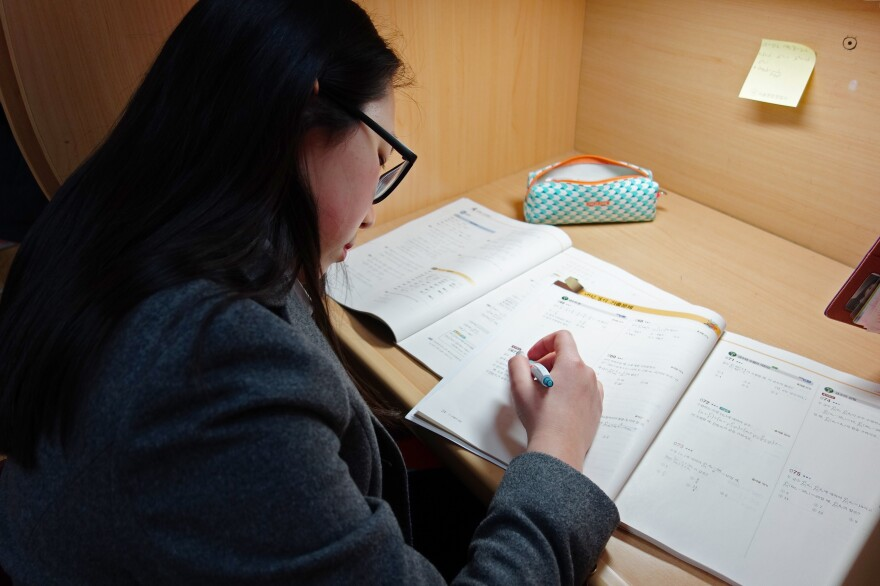 A student completes her workbook at study hall.