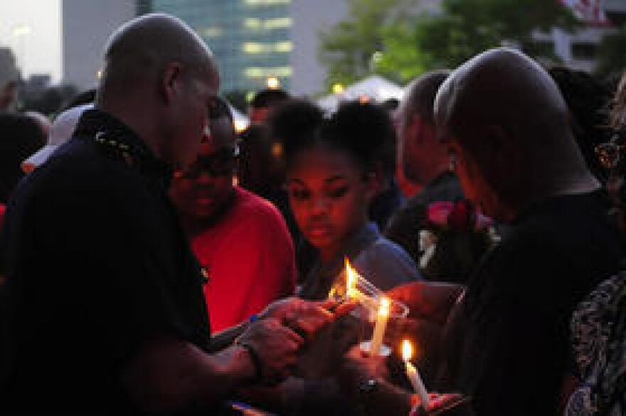 Dallas police officer lights the candles for attendees of the vigil on July 11, 2016.