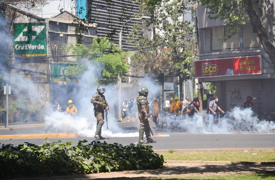 Riot police shoot tear gas and water cannons into a crowd of protesters in downtown Santiago on Monday.