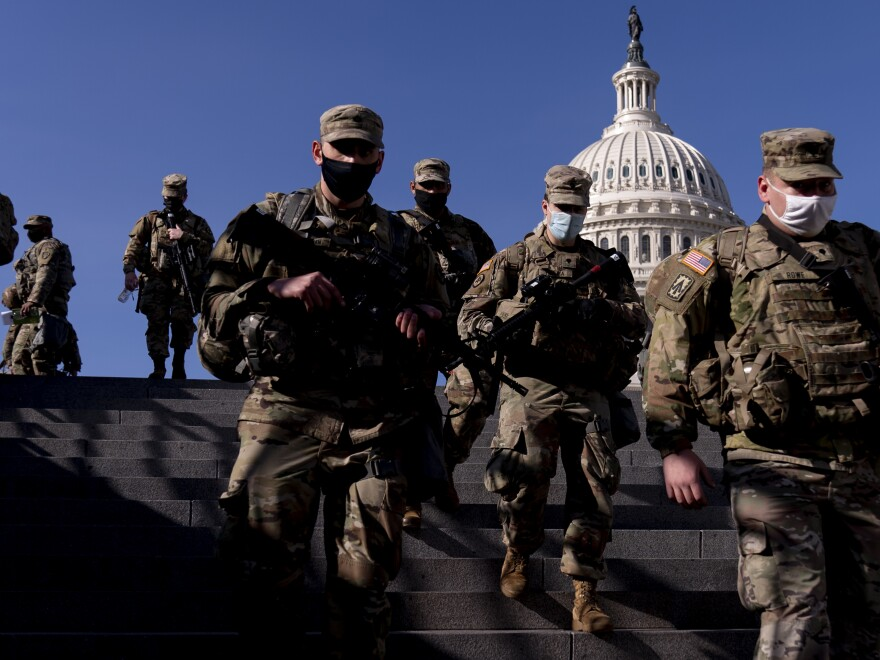 Members of the National Guard walk past the dome of the Capitol Building in Washington on Thursday.