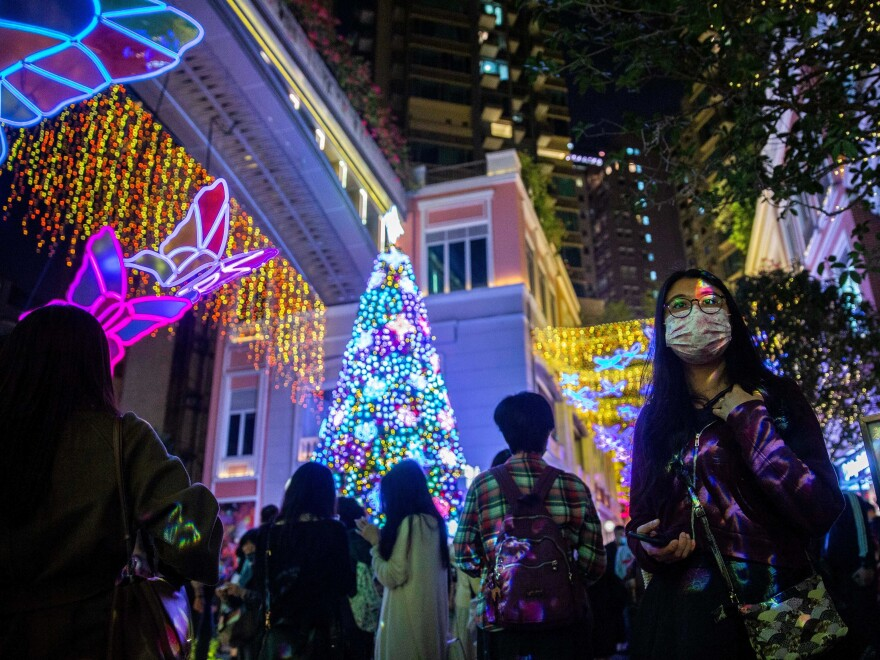 People wearing face masks walk past a Christmas display at a shopping mall in the Wanchai district of Hong Kong on Dec. 24, 2020.