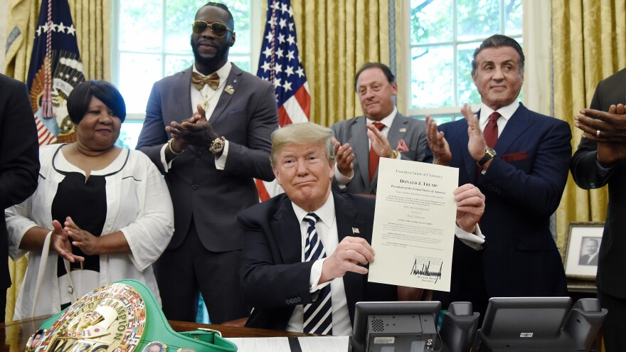 President Trump holds a signed Executive Grant of Clemency for boxer Jack Johnson in the Oval Office of the White House on Thursday, as (from left) Johnson's great-great niece Linda Haywood, boxer Deontay Wilder, Keith Frankel and actor Sylvester Stallone applaud.