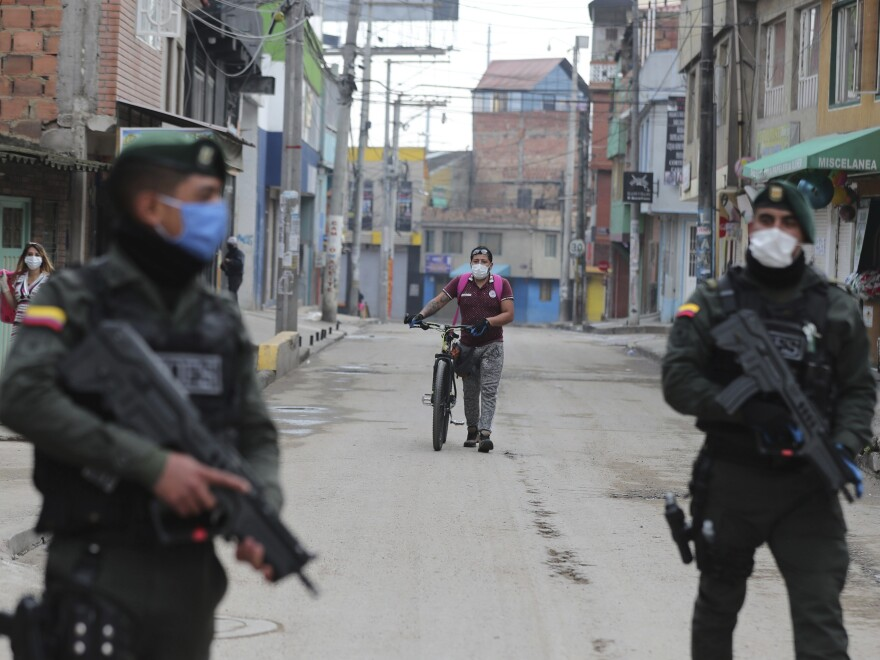 Police stand guard during a government order for residents to stay home, to help contain the spread of the new coronavirus, as a resident walks to a food store in Soacha on the outskirts of Bogotá, Colombia, on March 25.