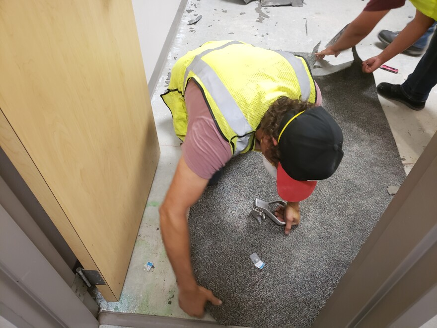 Inside of a permanent party dorm at JBSA-Lackland, workers rip up carpet as part of their mold remediation efforts.