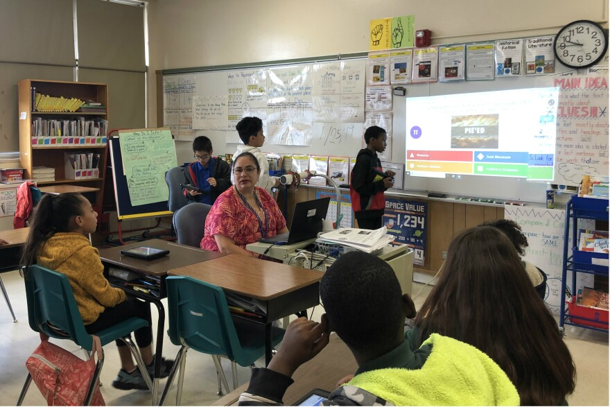 Master teacher Michelle Olivarri guides her third grade students through a computer game on the parts of a story in January 2019..
