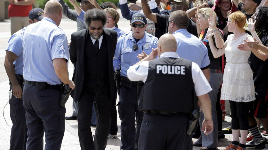 Activist Cornel West is arrested during a protest outside the federal courthouse in St. Louis. He and dozens of other protesters marking the death of Michael Brown in Ferguson, Mo., one year ago.