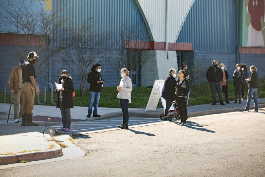 Austinites wait in a line to get a COVID-19 vaccine on Wednesday. The line wraps around the side of the Delco Activity Center building.