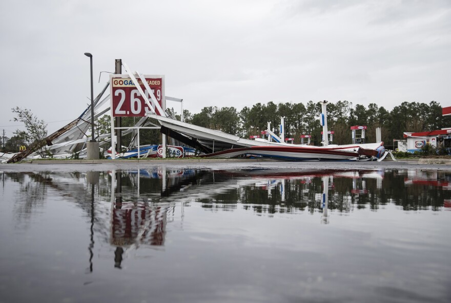 A damaged gas station is reflected in a puddle in Wilmington, N.C.