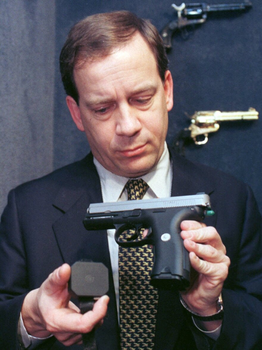 """Stephen Sliwa, then president of Colt, holds a prototype of the company's """"smart gun"""" at the Colt plant in West Hartford, Conn., in 1998."""