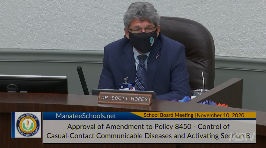 Dr. Scott Hopes wears a black mask at a school board meeting