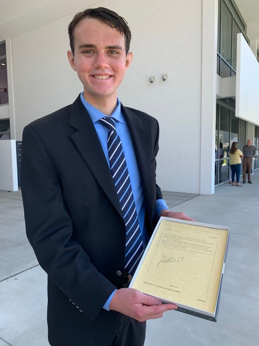 Mark Merwitzer holds signed copy of new Florida law