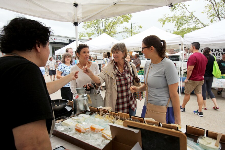 Ana Kelly offers a sample of freshly grilled Halloumi cheese to customers.