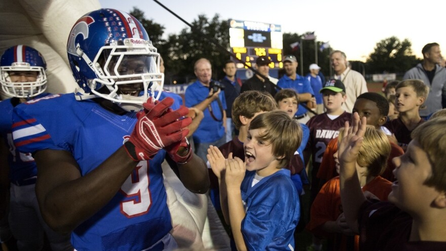 """Ellerbe, greeted by fans on the field. """"Everybody in your community, wherever you are in America, and every high school — they rally around the football team,"""" says Nate Jackson."""