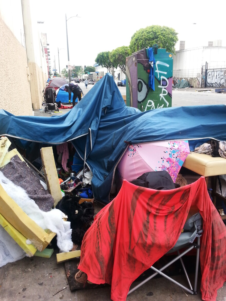 A pink umbrella peeks through a collapsed tent home on L.A's Skid Row.