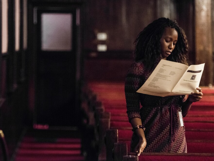 A woman reads a program during a memorial service remembering the victims of the mass shooting at Emanuel African Methodist Episcopal Church.