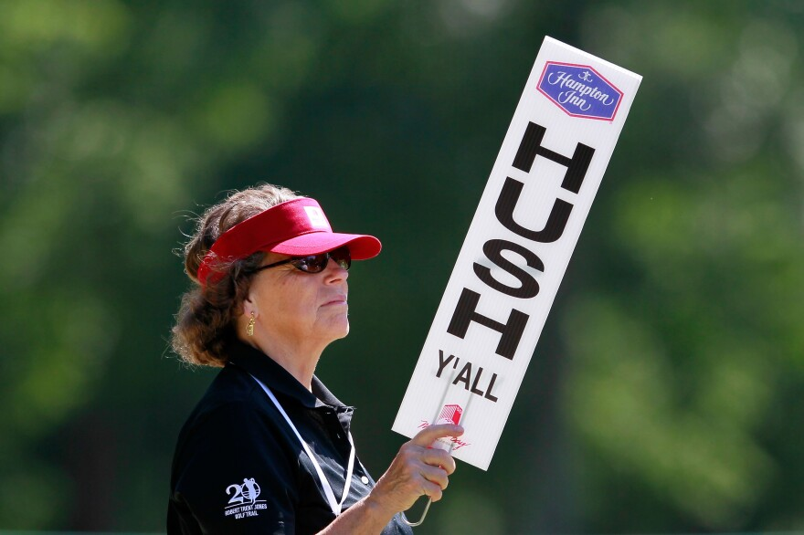 "A volunteer holds up a ""Hush Y'all"" sign at an LPGA golf tournament in 2012 in Mobile, Ala."