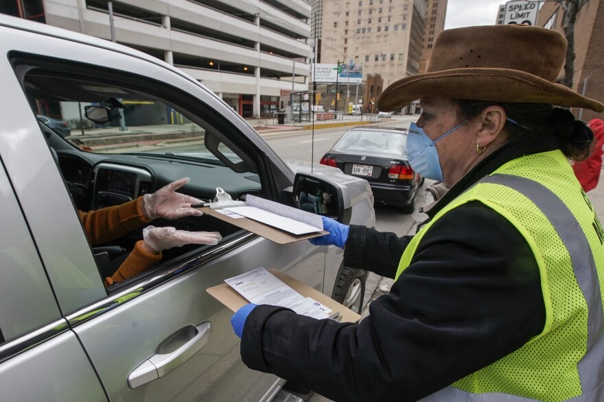 Jill Mickelson helps a drive up voter outside the Frank P. Zeidler Municipal Building Monday March 30, 2020, in Milwaukee. The city is now allowing drive up early voting for the state's April 7 election. The state is facing renewed calls to postpone the election amid the coronavirus outbreak.