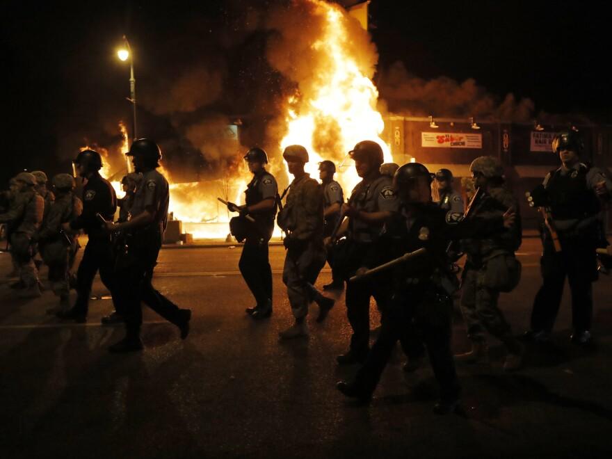 Police clear the street for firefighters during protests Friday, May 29, 2020, in Minneapolis. Protests continued following the death of George Floyd, who died after being restrained by Minneapolis police officers on Memorial Day.