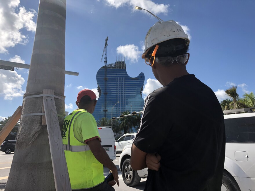 Seminole Hard Rock Hotel and Casino expansion construction workers Freddy Gomez and Jorge Varela look at the building in progress from across the street.