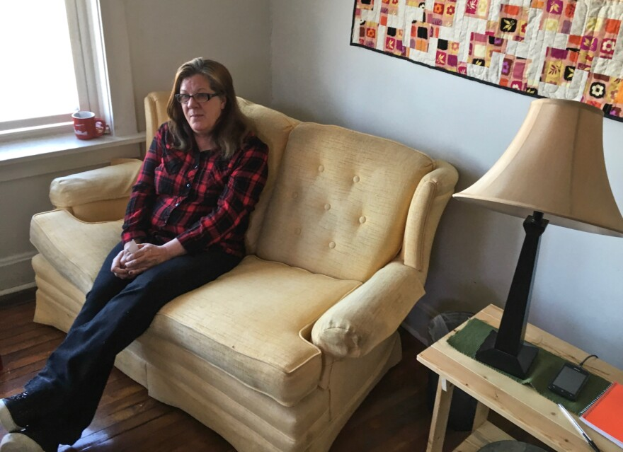 Ann Garcia, 54, poses on a couch she got from the Home Sweet Home furniture bank.