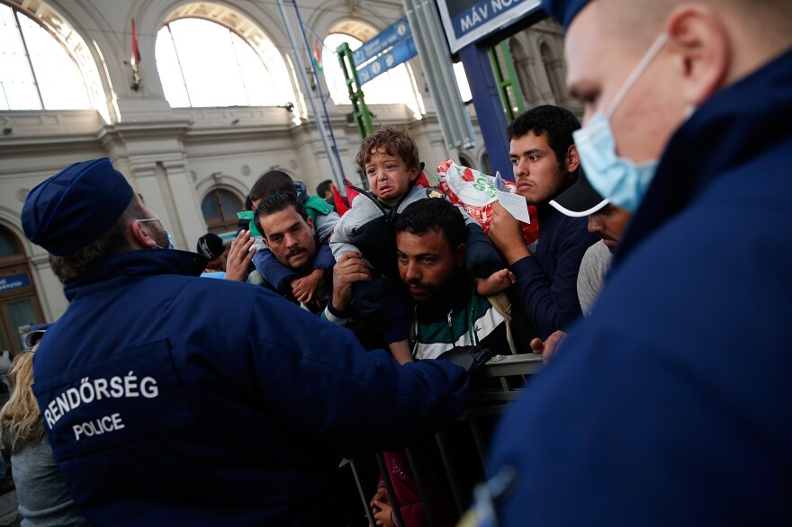 A boy sits on his father's shoulders, part of a crowd of migrants waiting to board a train leaving for the Austrian border at the Keleti railway station in Budapest.