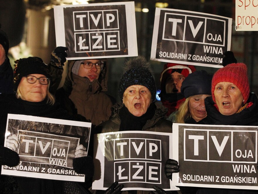 Protesters hold signs demanding the resignation of TVP chairman Jacek Kurski in Warsaw, Poland, on Jan. 26, 2019, blaming the atmosphere created by the government-controlled broadcaster's messaging for the  killing of of Gdansk Mayor Pawel Adamowicz.