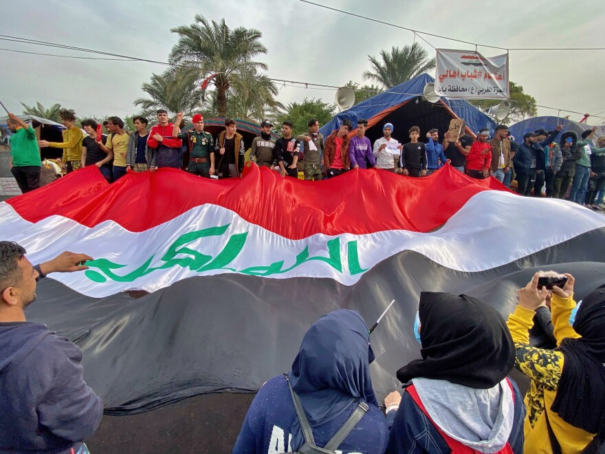 Anti-government protesters hold an Iraqi flag in Tahrir Square in Baghdad on Thursday. As Iraqis continue to demonstrate against their government, U.S. officials say Iran is stepping up attacks.