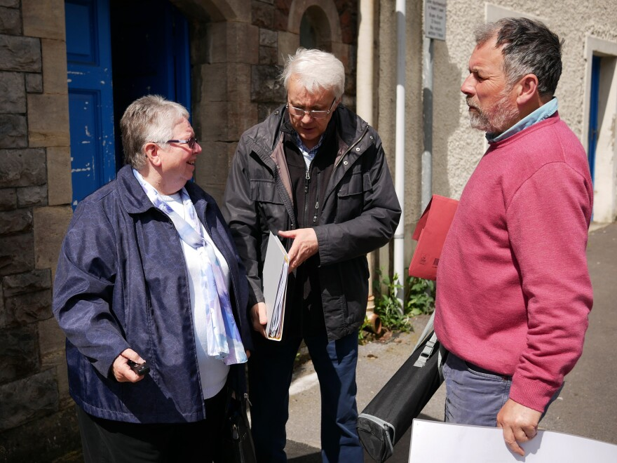 Jeff Britten (center), his wife Sharon and group treasurer Julian Rutter stand outside the Haverfordwest chapel where they organize their work settling Syrian refugees.